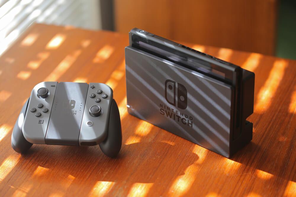 Nintendo Switch na cor cinza com controle ao lado sobre a mesa.