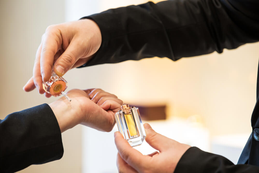 Imagem de uma pessoa aplicando perfume no punho de outra.