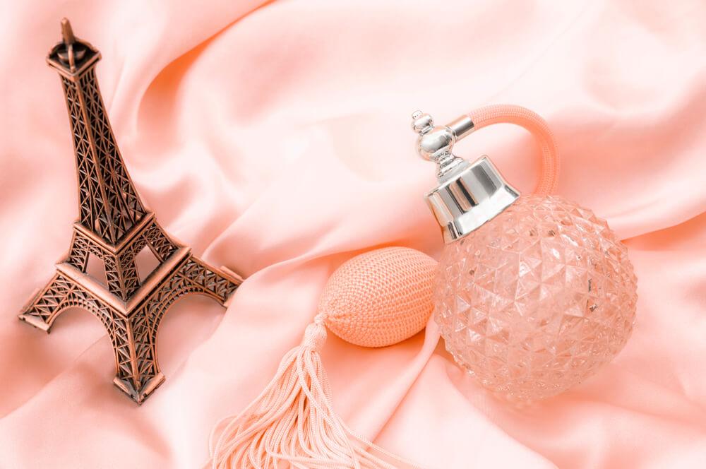 Um Frasco De Perfume E Uma Miniatura Da Torre Eiffel Sob Um Tecido De Cetim Rosa.