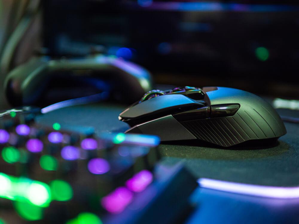 Mouse gamer ao lado do teclado, em cima do mousepad.