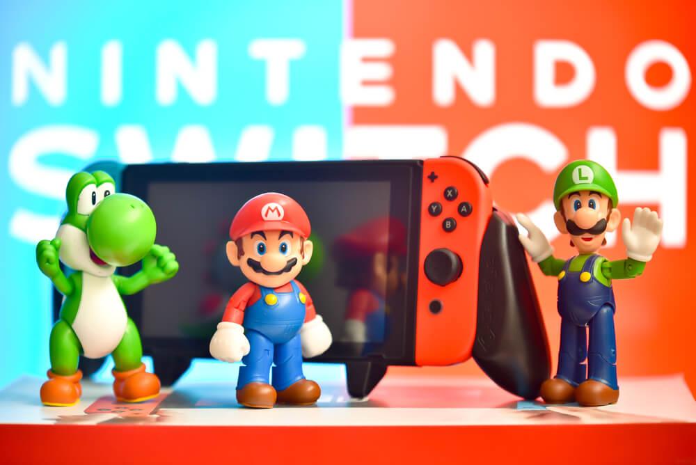 Nintendo Switch Em Exibição Com Personagens Dos Jogos Do Mario Ao Redor.