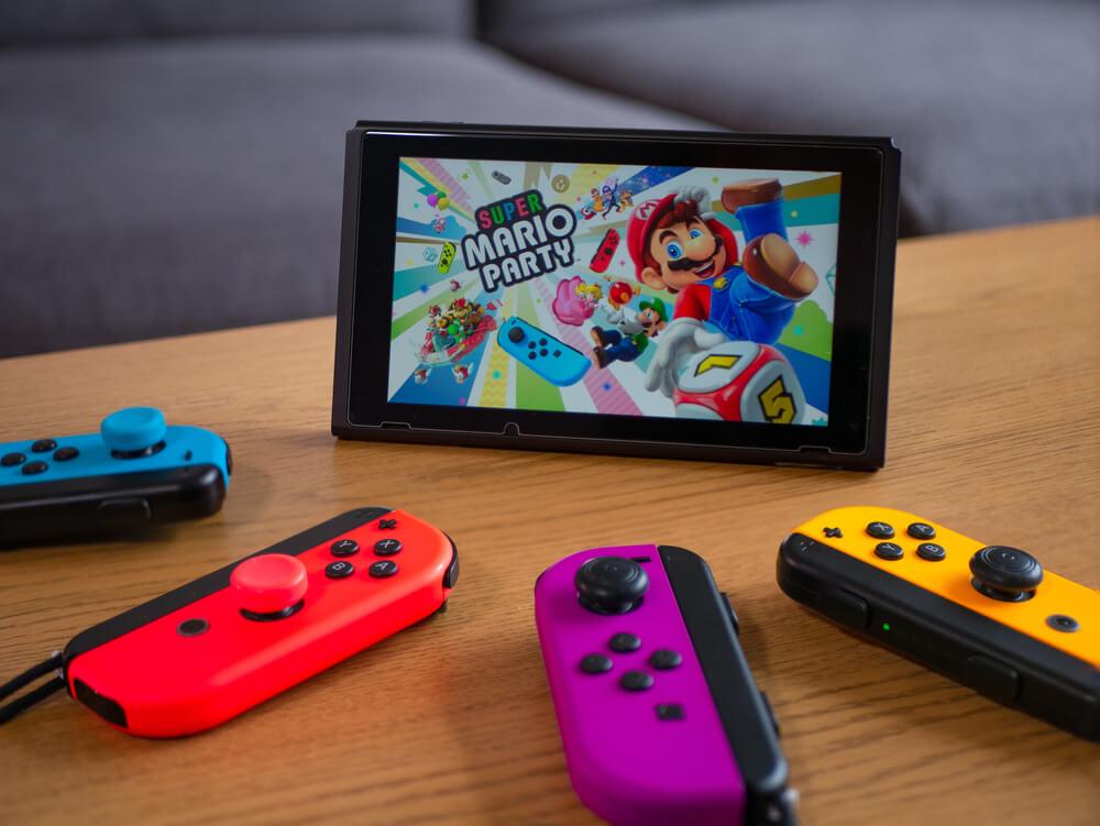 Mario Party iniciando em um Nintendo Switch. Ao redor, quatro controles coloridos.