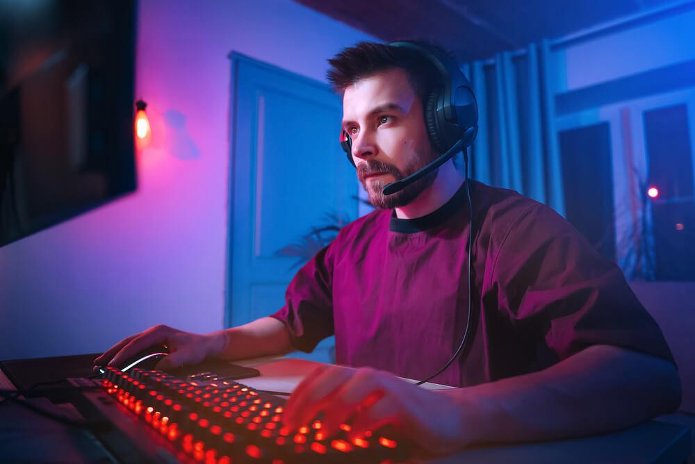 Homem jogando no computador com fone de ouvido.