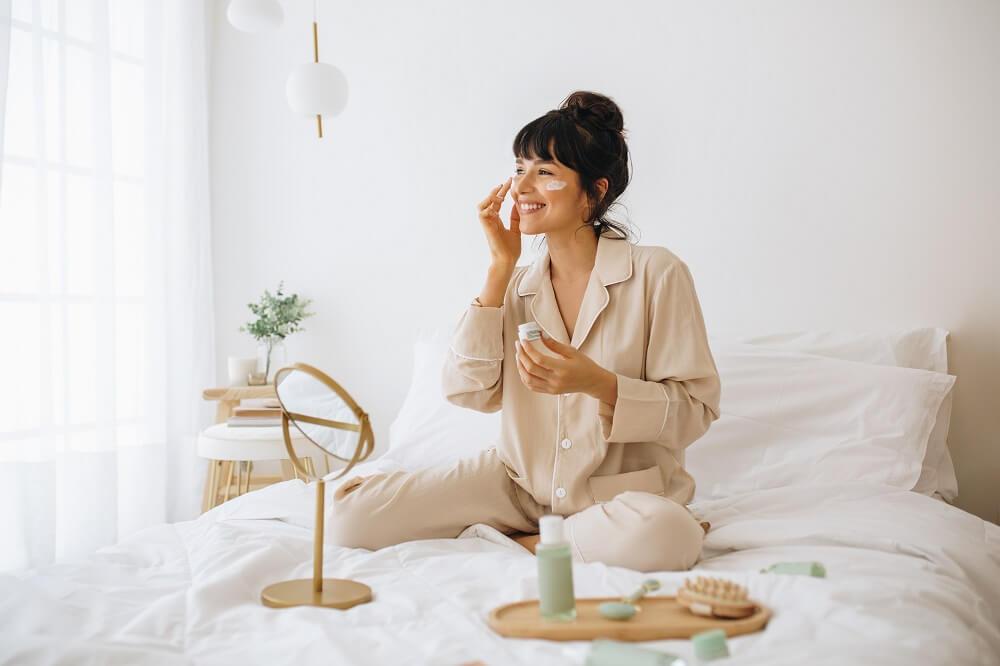 Mulher branca de pijama fazendo skincare sentada na cama