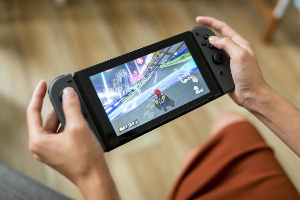 Pessoa jogando Mario Kart em um Nintendo Switch preto.