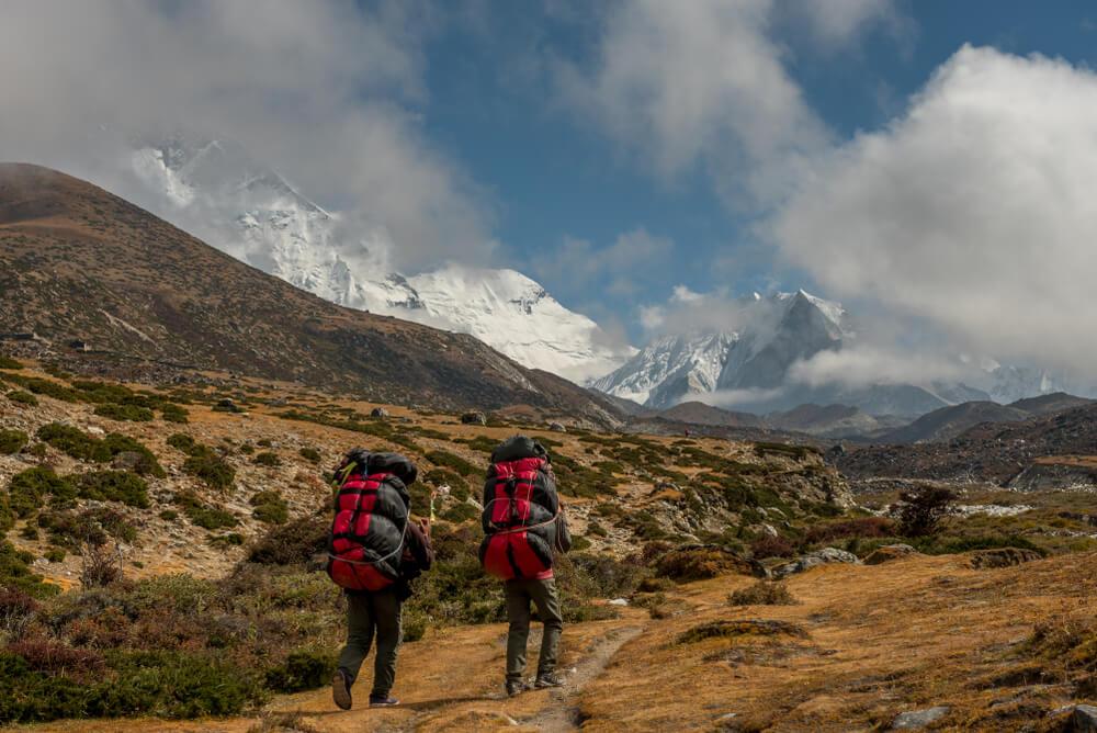 Duas pessoas em meio à montanhas, com mochilas de camping.