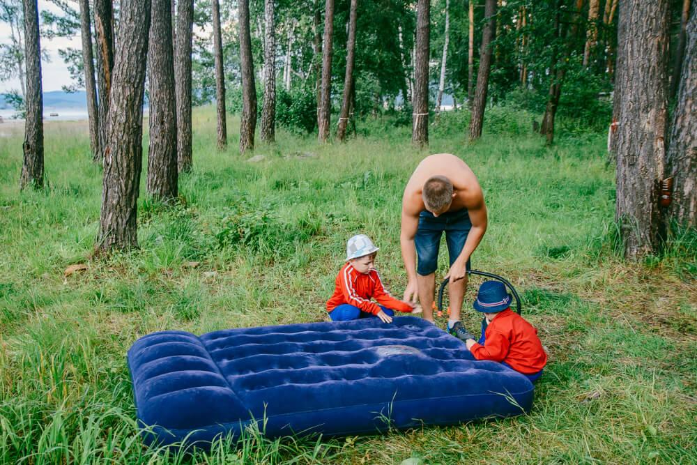 Homem e duas crianças em meio á uma floresta, enchendo um colchão inflável - um dos acessórios de camping.