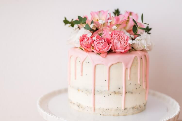 Bolo rosa com flores naturais no topo.