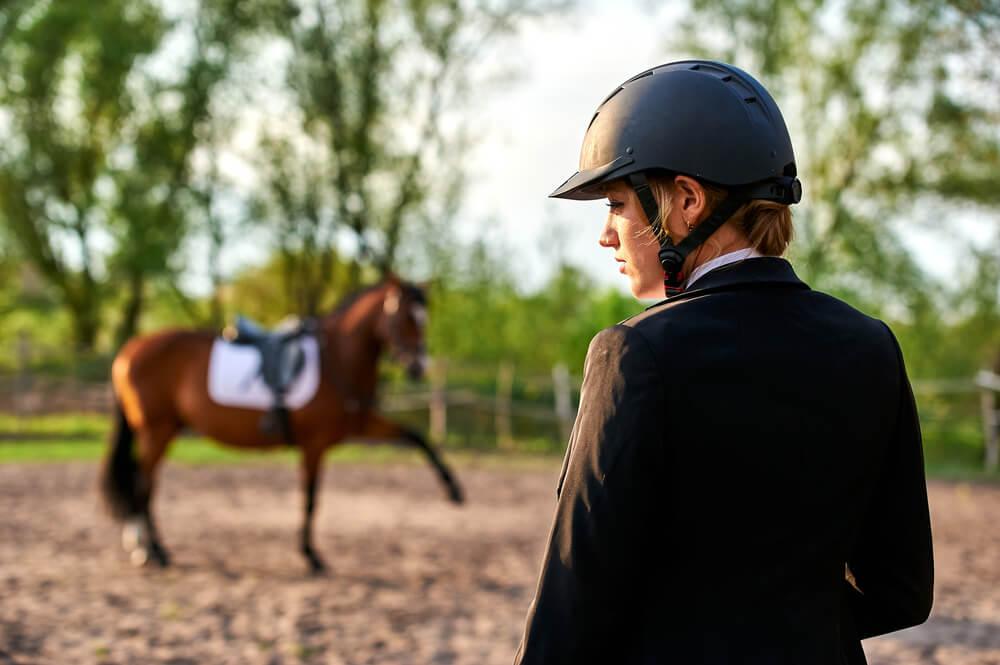 Mulher Utilizando Capacete Para Hipismo Em Primeiro Plano. Em Segundo Plano, Um Cavalo.