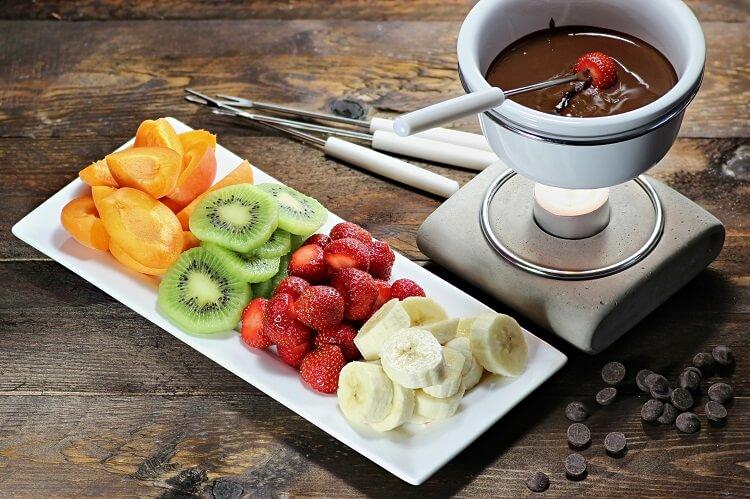 Fondue de chocolate amargo com frutas ao redor.