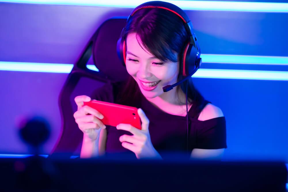 Mulher Sentada Em Uma Cadeira Gamer, Enquanto Mexe No Celular E Está Com Um Fones De Ouvido Gamers Hyperx.