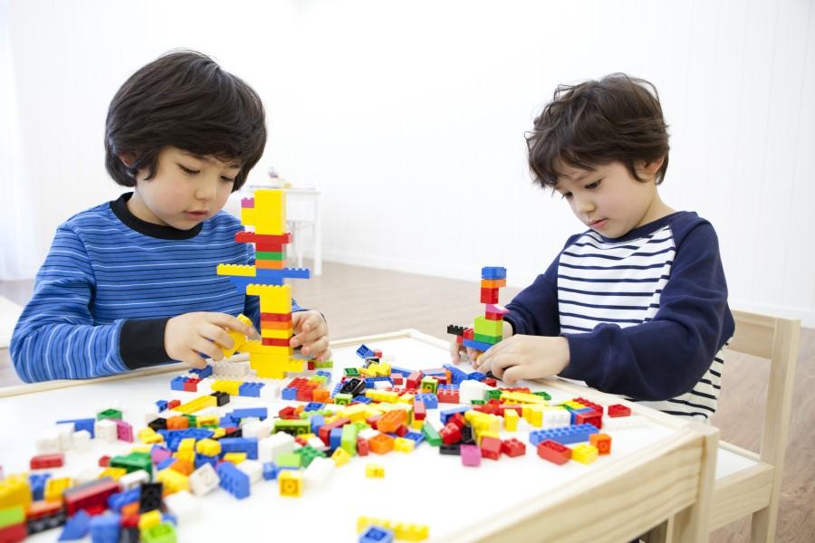 Duas crianças brincando com Lego em uma mesa.