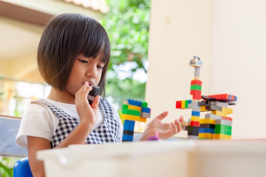 Menina brincando com peças de Lego.