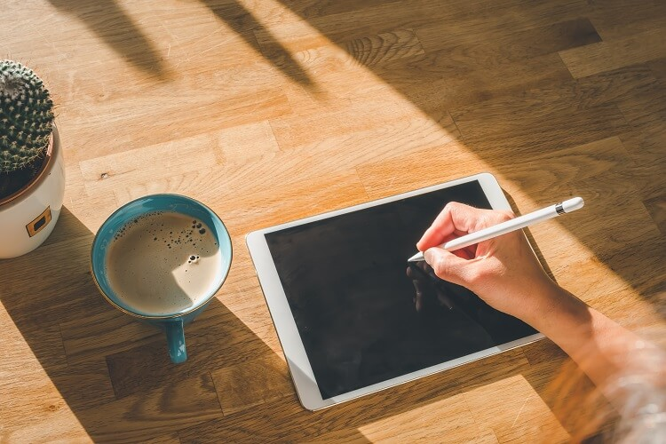 Mulher desenhando no ipad com um café do lado