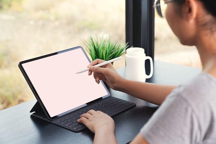 Mulher olhando para ipad com uma caneta de desenho na mão