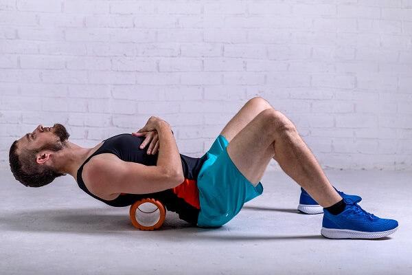 homem fazendo exercícios para a coluna com rolo de liberação miofascial