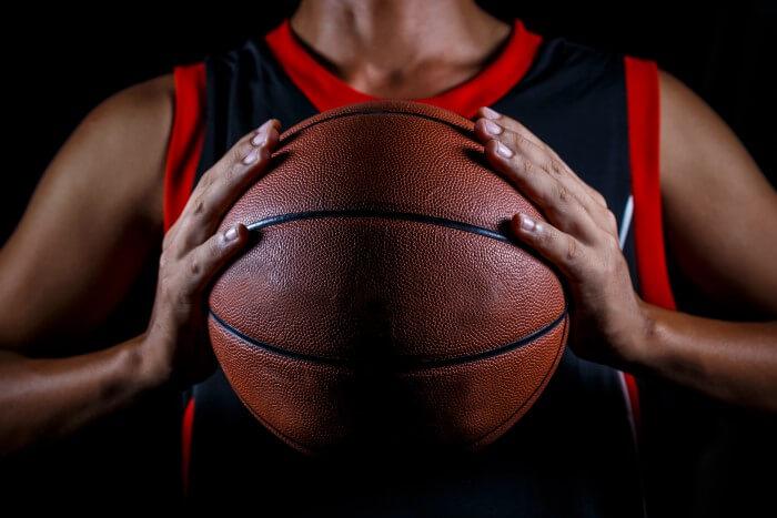 Homem segurando bola de basquete profissional