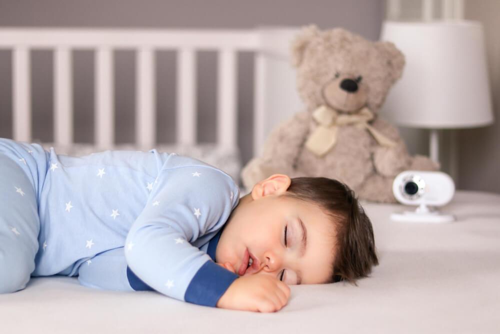 Bebê dormindo. Ao fundo da imagem, desfocados, vemos um urso de pelúcia e uma babá eletrônica monitorando o sono da criança.