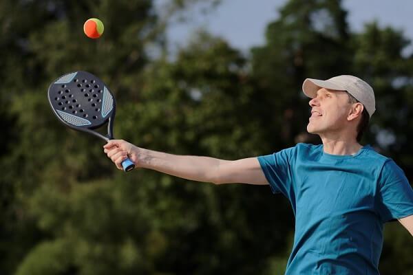 homem utilizando raquete de beach tennis para a prática da modalidade.