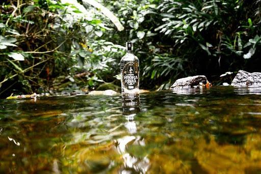 Foto da garrada do Gin Vitória Régia em meio a um lago.