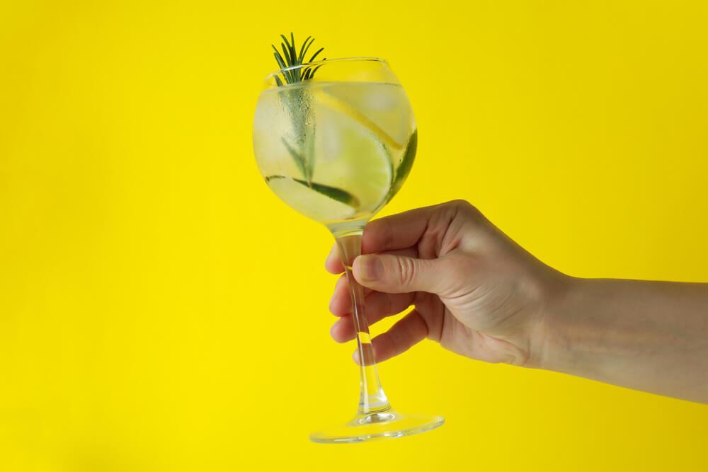 Uma Mão Segurando Uma Taça De Gin Tônica Com Limão E Alecrim, Em Um Fundo Amarelo.