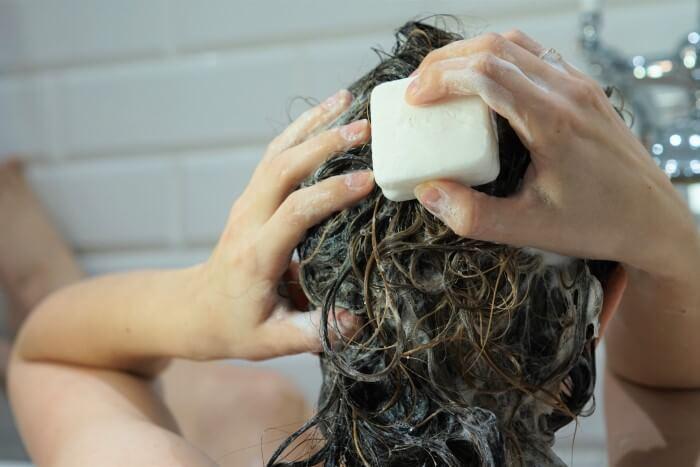 Mulher lavando o cabelo com shampoo em barra