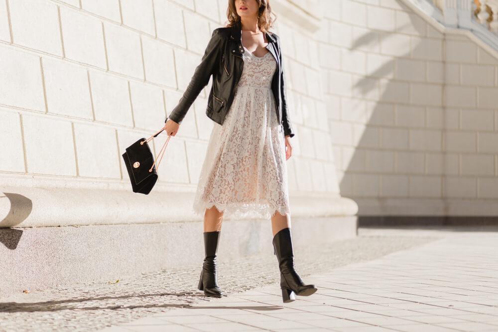 Na imagem vemos uma mulher utilizando vestido, bota e jaqueta de couro. Ela está segurando uma bolsa preta e está no meio de uma rua.