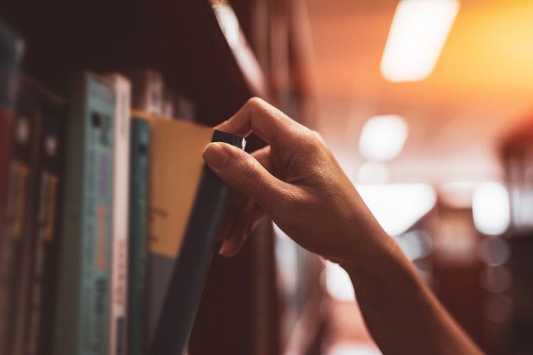 Mão retirando livro de estante