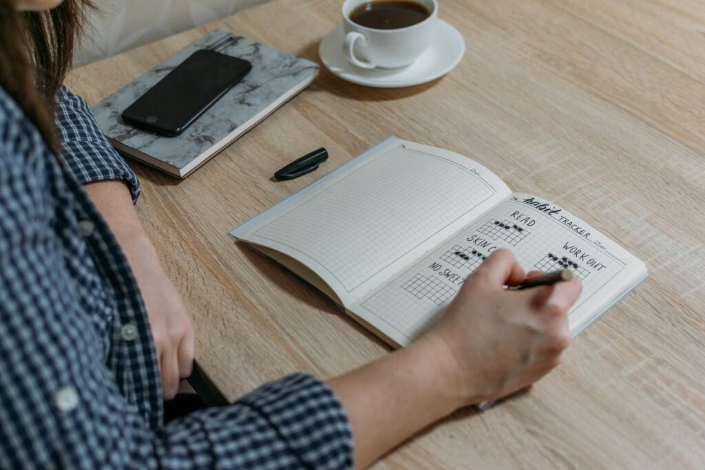 pessoa escrevendo em habit tracker