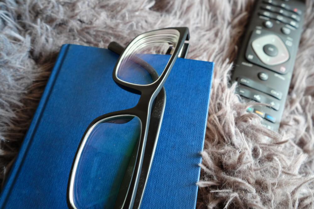 Na Imagem Vemos Um Livro De Capaz Azul. Em Cima Dele Está Um óculos De Grau. Ao Lado, Há O Controle De Uma TV.
