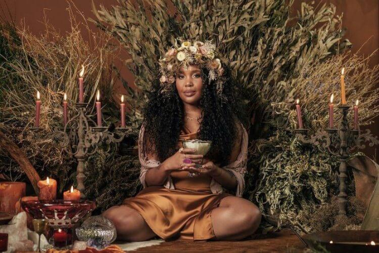 Mulher Sentada Ao Lado De Castiçais E Plantas Com Uma Taça Na Mão