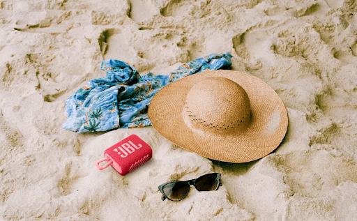 Foto de um chapéu, um óculos, uma canga e uma caixa de som JBL em uma areia.