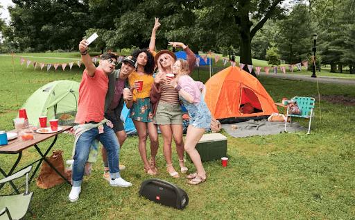 Amigos reunidos no campo, festejando, com uma caixa de som JBL.