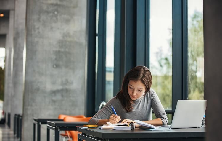 Mulher asiática estudando em biblioteca