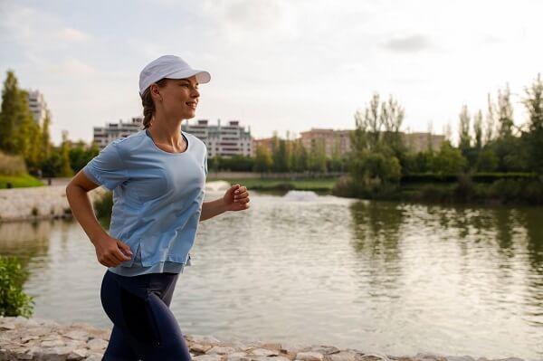 mulher correndo perto de um rio com roupas de corrida feminina, com camiseta azul claro, legging azul escuro e boné branco