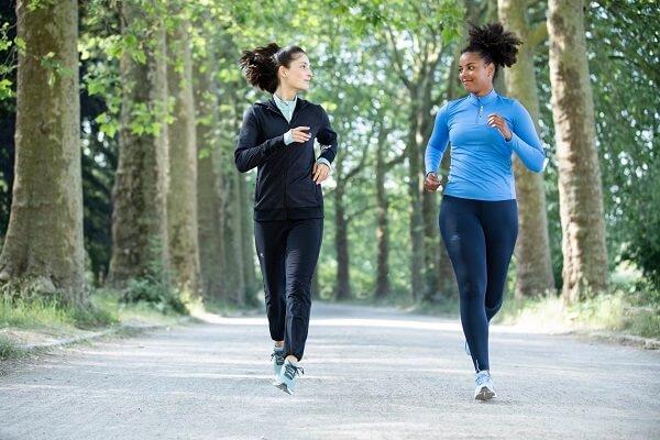 duas mulheres correndo em um parque usando roupas de corrida feminina, com calça, jaqueta e camiseta de manga longa