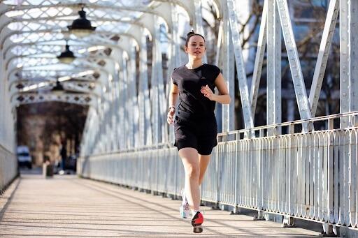 mulher correndo em uma ponte e vestindo roupas de corrida feminina, com camiseta preta e short preto