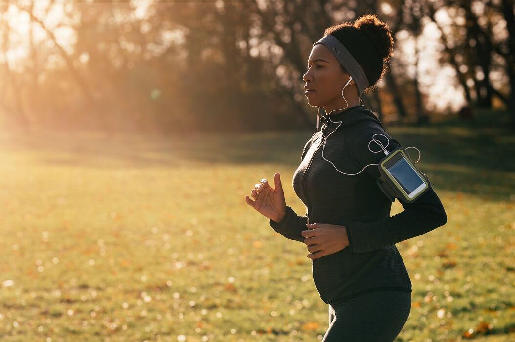 Mulher Correndo Em Um Parque Vestindo Roupas De Corrida Feminina, Com Fone E Braçadeira Para Celular