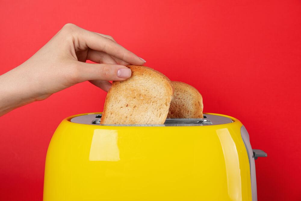 Imagem De Uma Torradeira Amarela. Uma Mão Está Colocando Um Pão Nela. Ao Fundo, Vemos Uma Parede Vermelha.