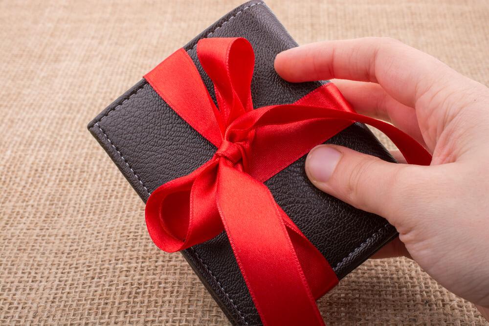 Imagem de uma carteira preta com um laço de fita vermelho.