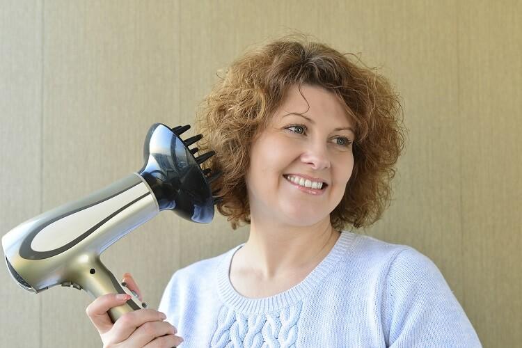 Mulher arrumando ondas com secador de cabelo com difusor