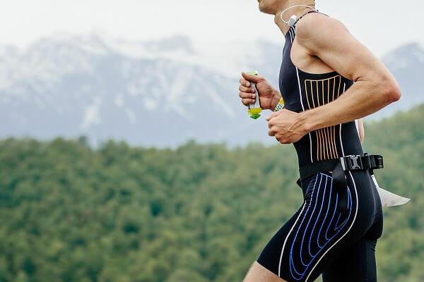 corredor em prova de montanha segurando gel de carboidrato