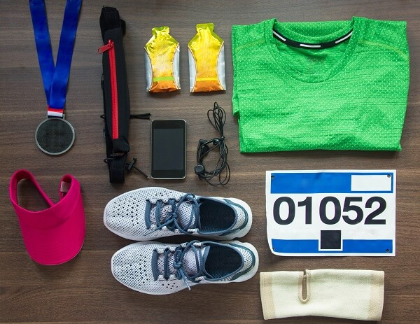 kit de prova de corrida de rua com gel de carboidrato, tênis, número de prova, medalha, viseira rosa e camiseta verde