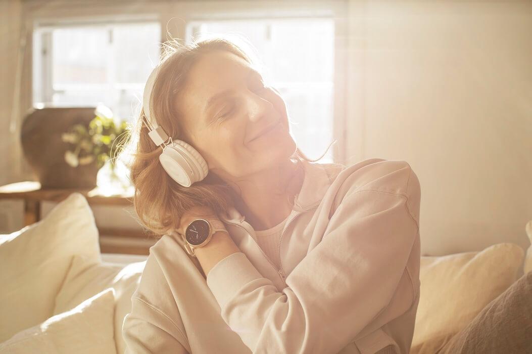 Mulher Ouvindo Música Com Headphone E Com Relógio Polar Ignite 2 No Pulso Esquerdo.